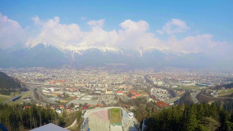 Time-lapse of busy city near mountains, popular ski resort, aerial pan, travel Footage