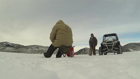Adult friends ice fishing winter mountain lake HD 0230 Stock Video Footage