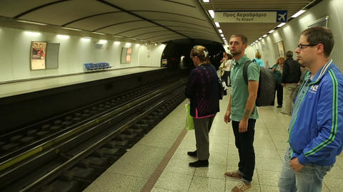 Commuters waiting on platform, subway train arriving, people travel to work Live Action