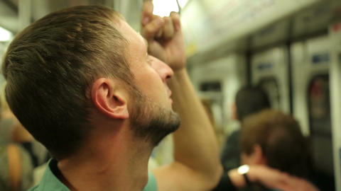 Tired male passenger reading advertisements inside subway train during rush hour Footage