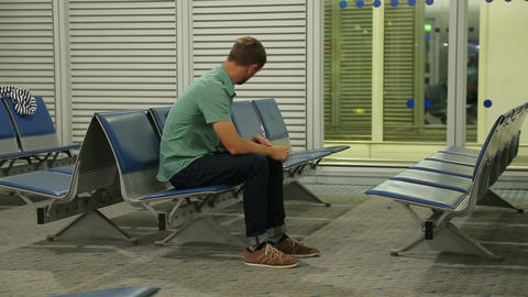 Bored passenger waiting for bus, checking e-mail on smartphone, reading news Footage