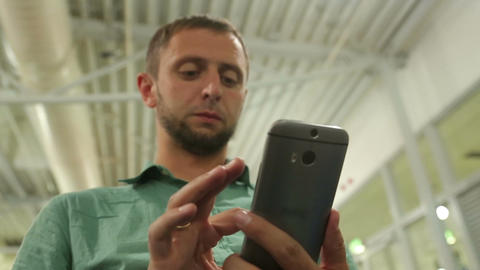Young male typing message on smartphone, dialing number to make phone call Footage