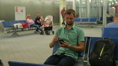 Man sitting at waiting room, airport or railway station, checking time on phone Footage