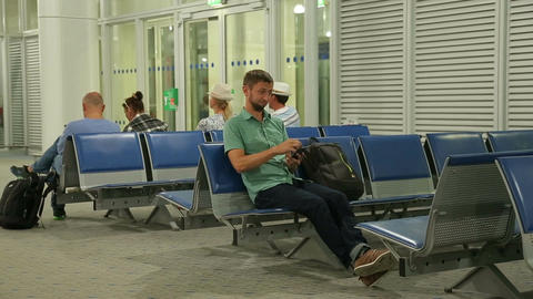 Happy guy checking time on smartphone clock, man walking for flight registration Footage