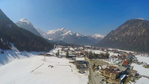 Small Alpine resort town at lakeside, huge mountains, snowy peaks, fast motion Footage