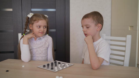 Children play checkers at the table. Brother and sister play checkers together Live Action