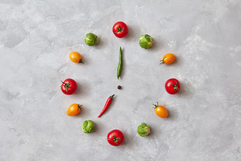 Moving colored vegetables make up a clock with moving arrows from chili pepper Live Action