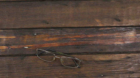 Modern spectacles lie on the old wooden surface. Zoom Live Action