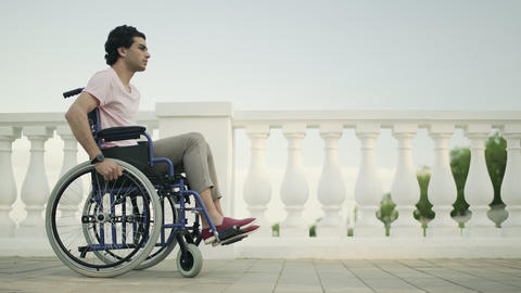 Young man in a wheelchair rides along a path in a public garden Live Action