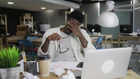 Tired man feeling sleepy at coworking. Portrait of black man falling asleep Live Action