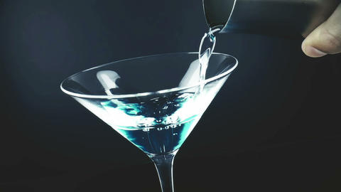 pouring blue fresh alcohol cocktail drink glass with on blue light tint background, shot slow Live Action