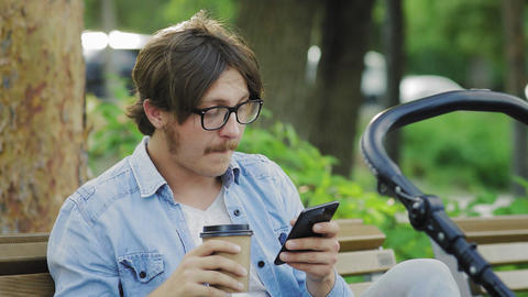 Baby is sleeping in a stroller, father is using a cellphone and drinking coffee Live Action