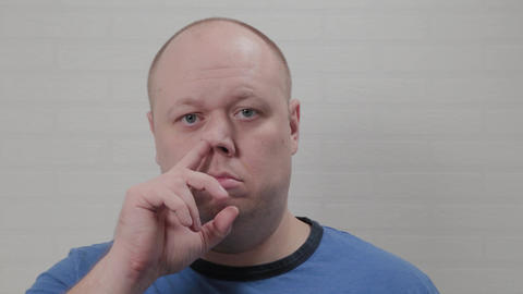 A bald man picks his nose at the camera. Portrait of a bald man Live Action