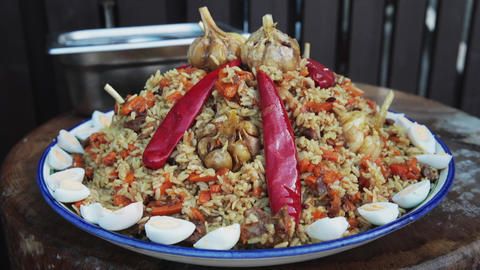 National Uzbek dish pilaf, pilaw, plov, rice with meat in big pan. Ready dish on Live Action