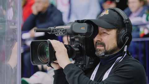 cameraman with equipment films hockey game on ice rink Live Action