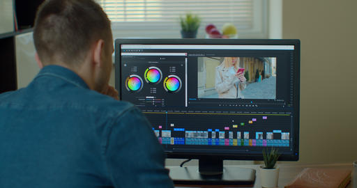 Man working on computer Color Correction Post Production video or photo in Live Action