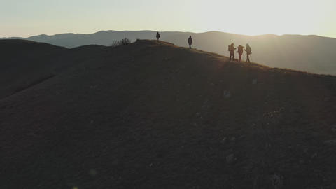 aerial filming of a group of tourists walks up the hill in the sunset Live Action