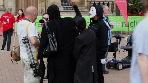Woman wearing burqa looking at photographer's portfolio during a public event Live Action