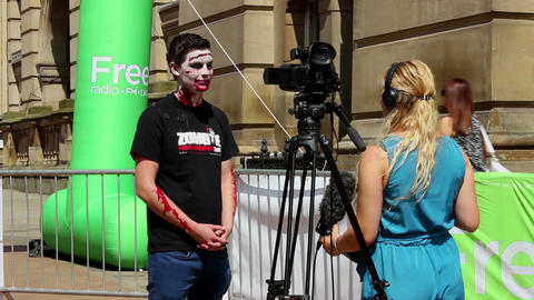 Zombie interview - woman with the camera interviewing zombie guy Live Action