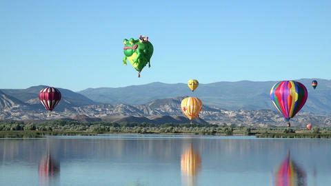Colorful hot air balloons over mountain valley lake 4K 054 Footage
