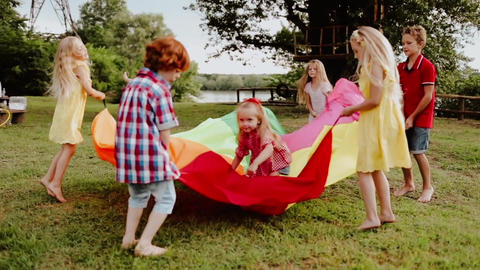 Children playing and jumping and waving play parachute in slo mo video Live Action