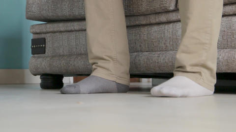 a man with unmatched socks get up from a couch Live Action
