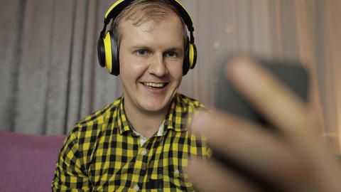 Young man making selfie, talking, video call at home in wireless headphones Live Action