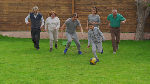 Family plays football at home on the meadow. The concept of family, sport and a Live Action