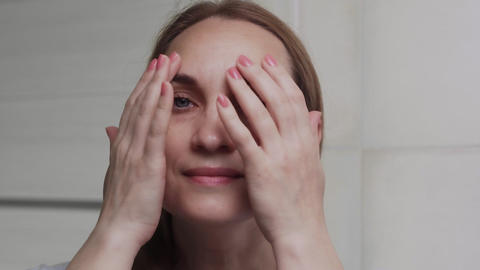 Caucasian Adult woman looks at the camera in the bathroom. Face wash, skincare Live Action