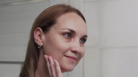 Caucasian woman in front of a mirror in the bathroom. Face wash, skincare Live Action
