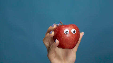 Red apple with eyes in a woman hand close-up. Apple shakes and twists eyes on a Live Action