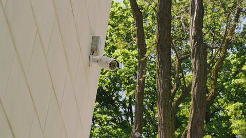 Professional video of security camera in the park. Hidden camera on the wall Live Action