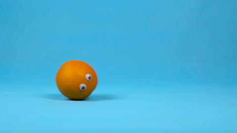 Orange with eyes rolls slowly. Orange with rolls on a blue background. Slow Live Action