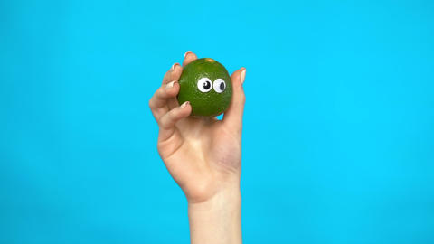 Lime with eyes in a woman hand close-up. Lemon shakes and twists eyes on a blue Live Action