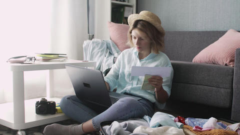 Young girl with laptop checks departure dates, getting ready for road trip Live Action