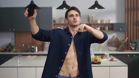 Portrait of cheerful man enjoying dance on kitchen. Sexy man smiling to camera Live Action