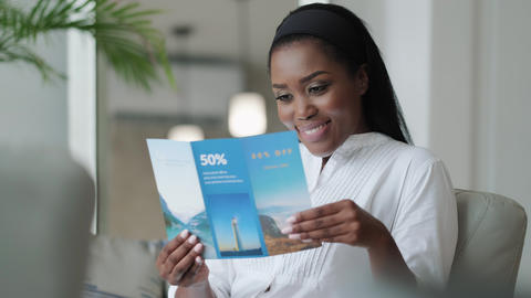 01 Black Woman Reading Travel Flyer And Planning Holidays Trip Live Action