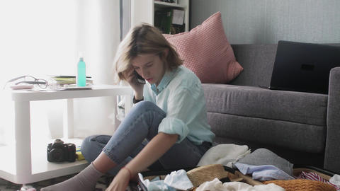 Young woman packing suitcase in home, getting ready for road trip, preparing Live Action