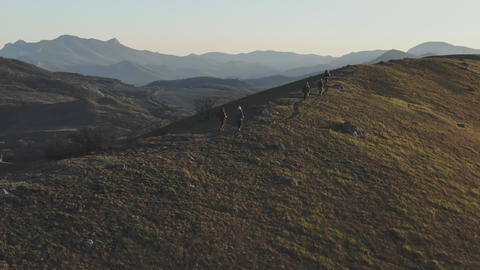 aerial shooting of a group of people walking along a trail on top of a hill at GIF
