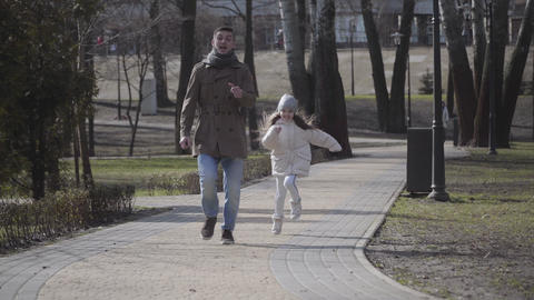 Cheerful little girl running after young joyful man imitating fear. Happy father Live Action