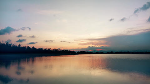 Red sunsets over lake. Red and pink sky with clouds. Summer sunset seascape. 4k Live Action