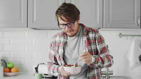 Man with glasses is eating helthy diet salad at kitchen Live Action