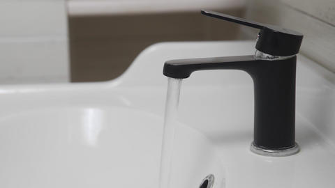 Male hand turning black water tap for pouring water into sink in bathroom. Water Live Action