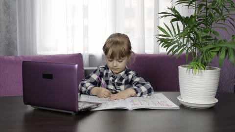 Girl learning online lessons using digital laptop computer. Distance education Live Action