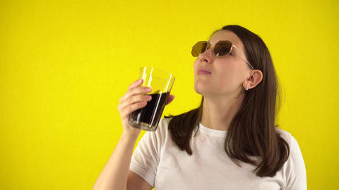 A young woman is holding a glass of soda. Pensive girl in a white T-shirt and Live Action