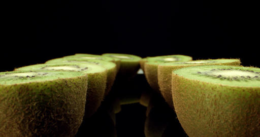 fresh kiwi fruit cut in half super macro high quality close up shoot fly over 4k shoot on dark Live Action