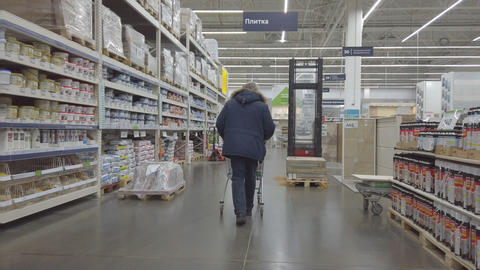 Man walks with a cart through a large supermarket of construction materials Live Action