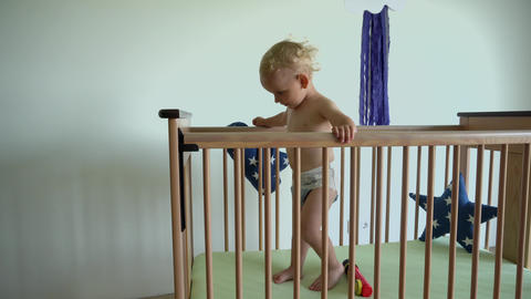 Hyperactive baby boy moving in crib. Alone child have fun in bed. Gimbal motion Live Action