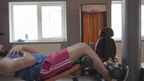 Side view of young Middle Eastern man pumping press using fitness equipment Live Action