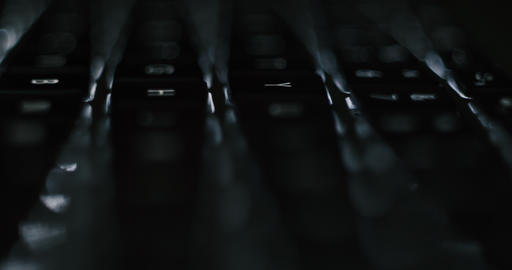 Macro footage of typing on illuminated laptop keyboard in the night - endless office programming Live Action